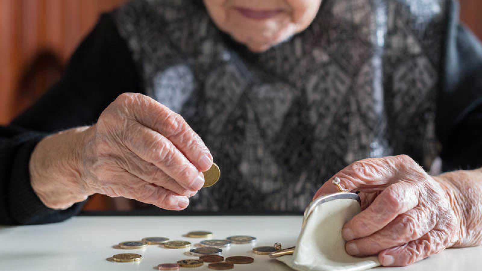 Una mujer mayor cuenta las monedas de su monedero