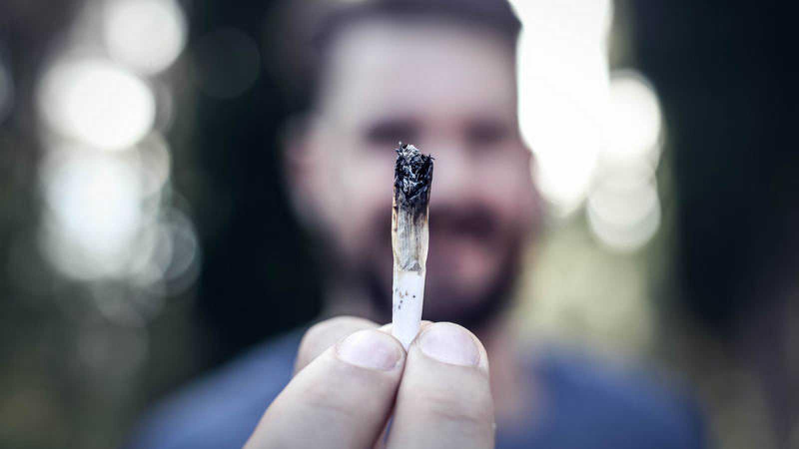 Un hombre sostiene un porro de marihuana