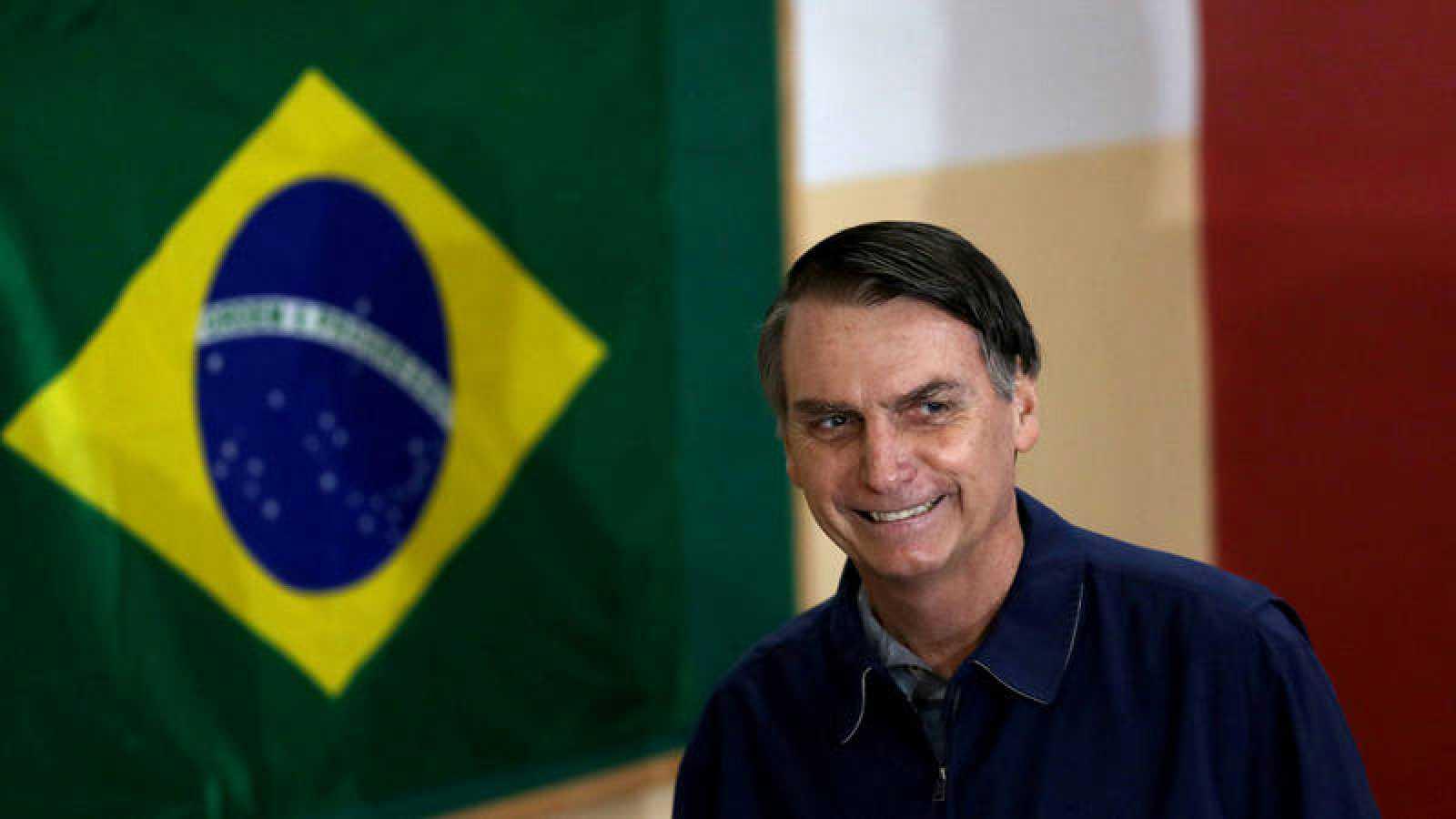 El candidato de extrema derecha, Jair Bolsonaro, pasa delante de una bandera de Brasil.