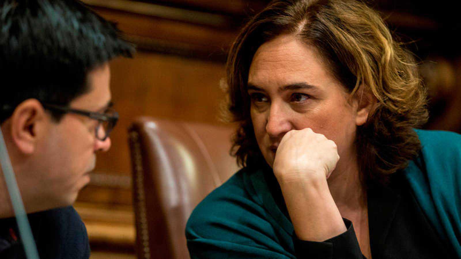 La alcaldesa de Barcelona Ada Colau, habla con el primer teniente alcalde, Gerardo Pisarello, durante el pleno del Ayuntamiento.