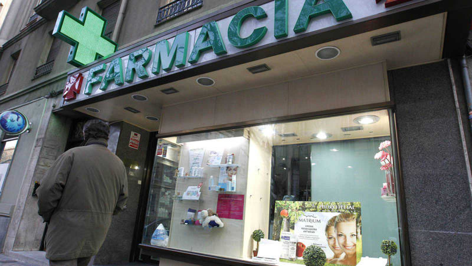 Un hombre camina ante una farmacia situada en la madrileña calle de Ríos Rosas
