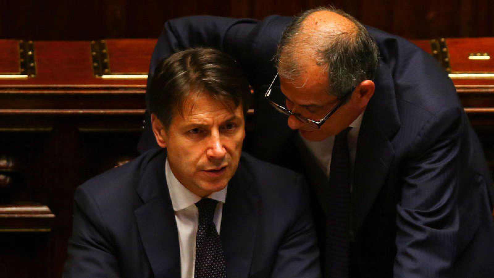 El primer ministro italiano, Giuseppe Conte, conversa con su ministro de Economía, Giovanni Tria