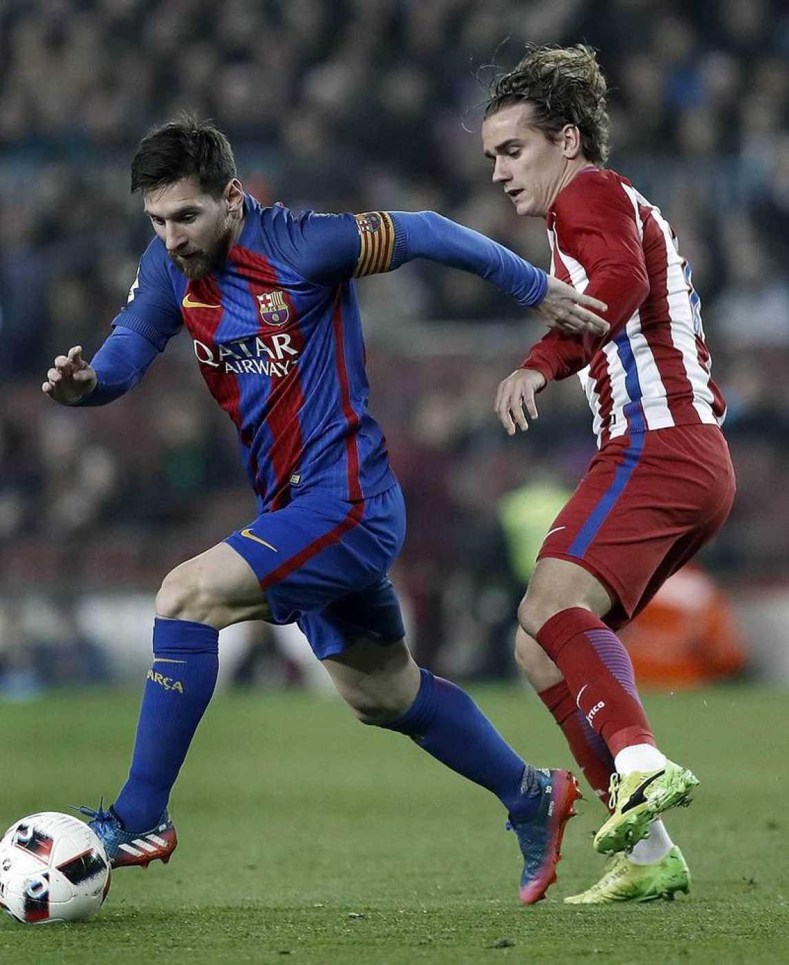 El delantero del FC Barcelona Leo Messi (i) controla el balón ante el del Atlético de Madrid Antoine Griezmann durante un partido de 2017
