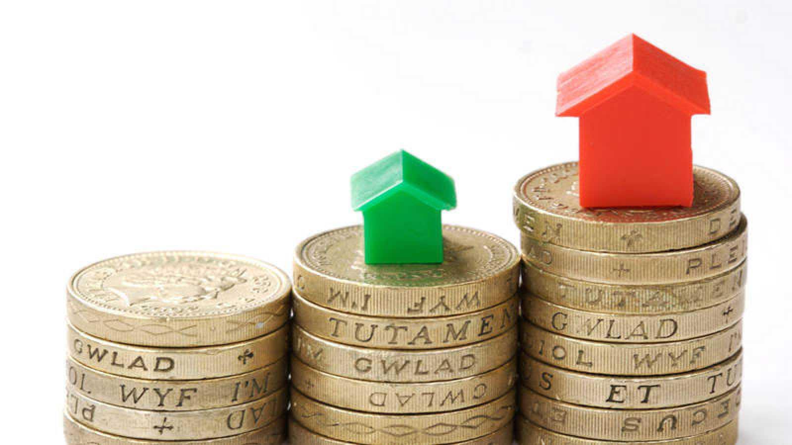 Flecha ascendente sobre monedas con ilustraciones de casas.