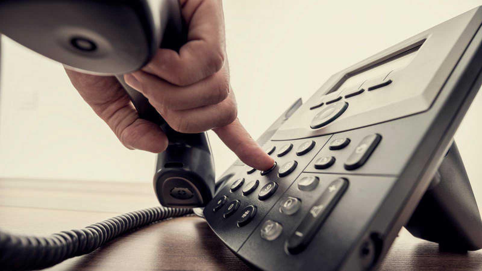 Un hombre marcando un número de teléfono