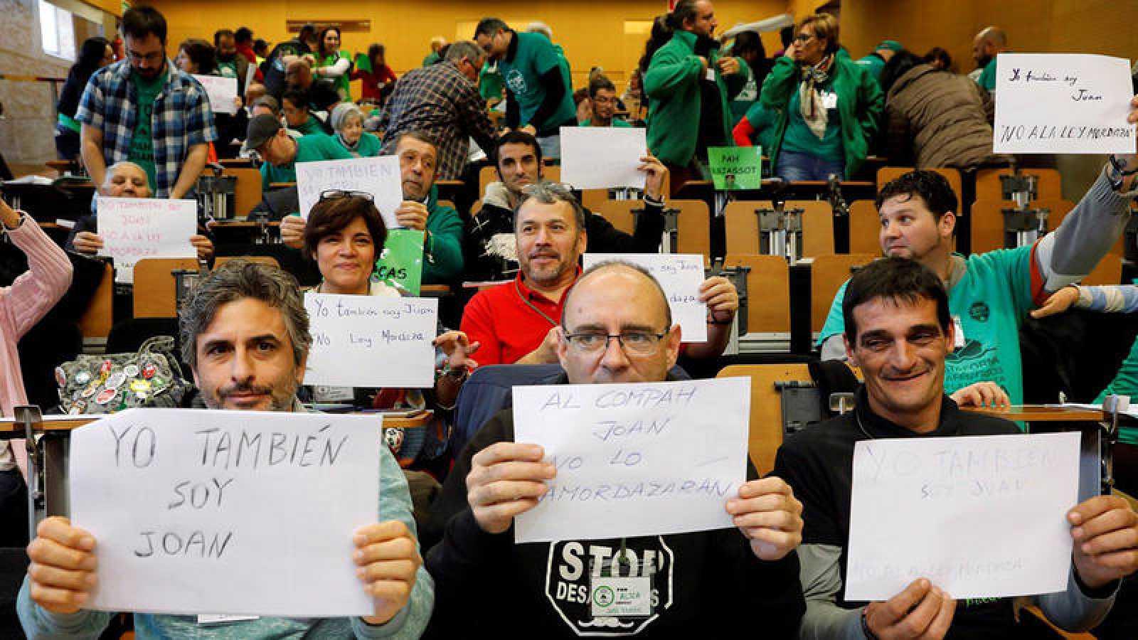 """Miembros de la Plataforma de Afectados por la Hipoteca (PAH) muestran carteles con el lema """"Yo también soy Joan"""" al finalizar su asamblea estatal en Valencia. EFE/Kai Försterling"""