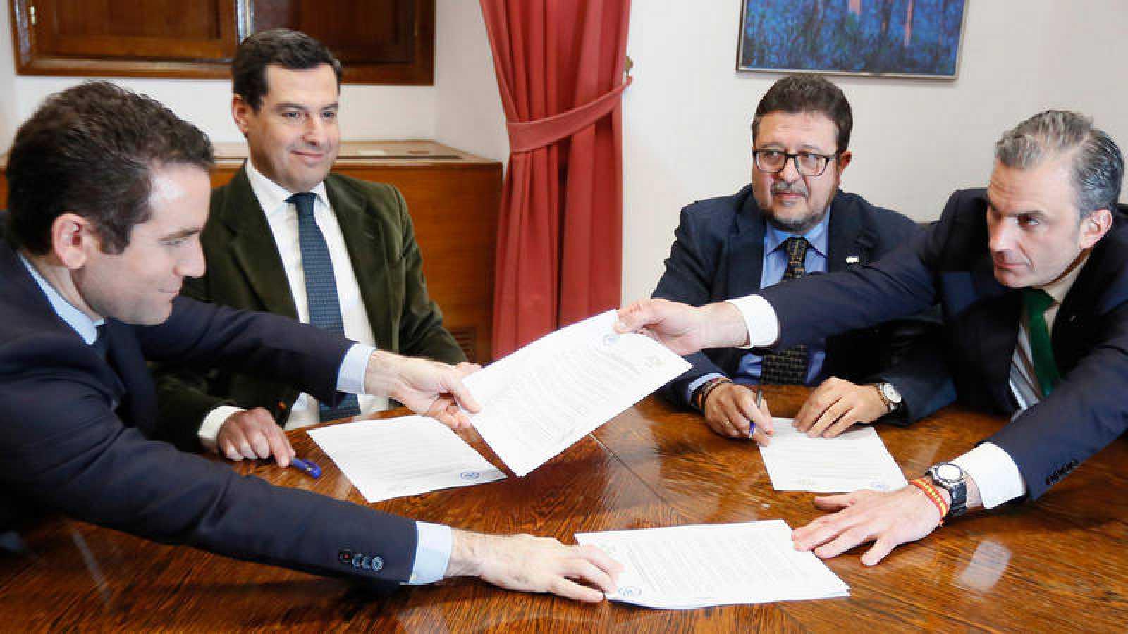 Los secretarios generales del PP, Teodoro García Egea (i), y de Vox, Francisco Javier Ortega Smith (d), intercambian unos documentos en presencia de los líderes andaluces del PP, Juanma Moreno (2i) y de Vox, Francisco Serrano