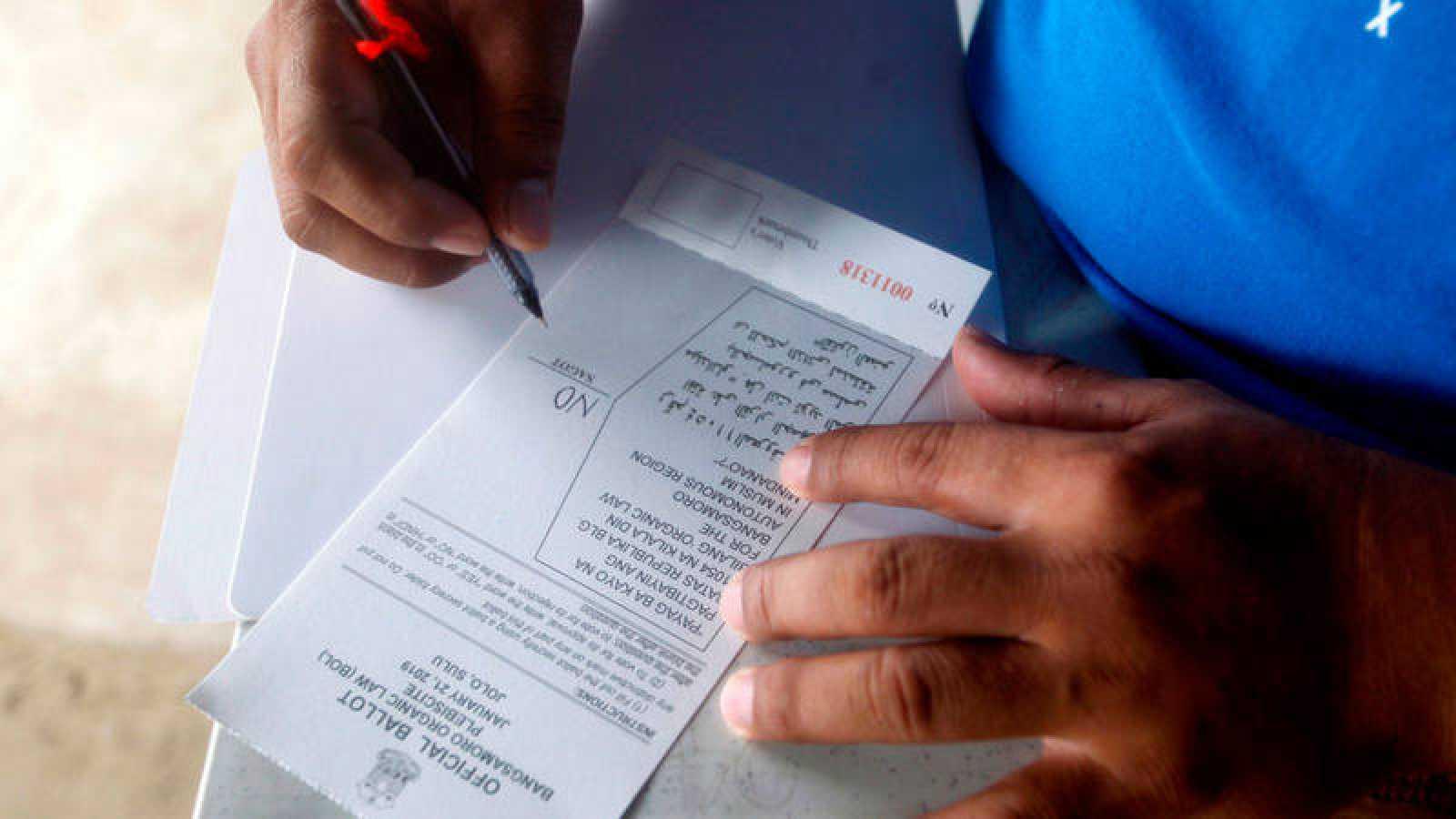 Un lugareño rellena su papeleta en un colegio electoral mientras participa este lunes en el plebiscito sobre la Ley Orgánica de Bangsamoro, en la localidad de Jolo (Filipinas).