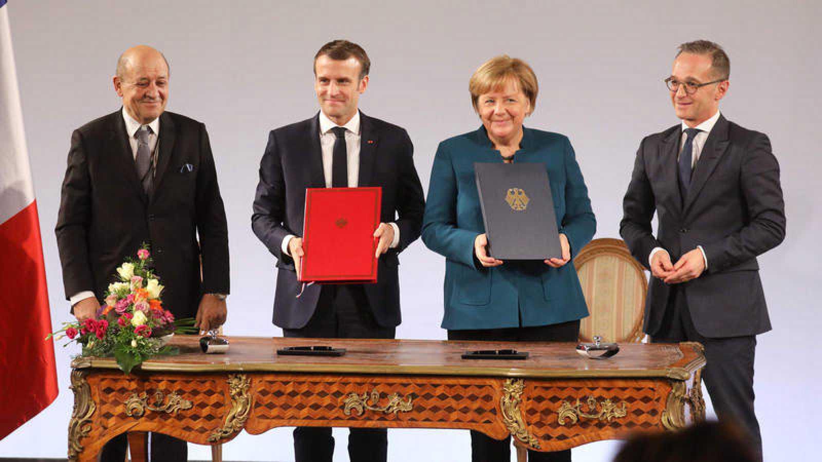 El presidente francés, Emmanuel Macron, y la canciller alemana, Angela Merkel sostienen el tratado bilateral firmado por ambos