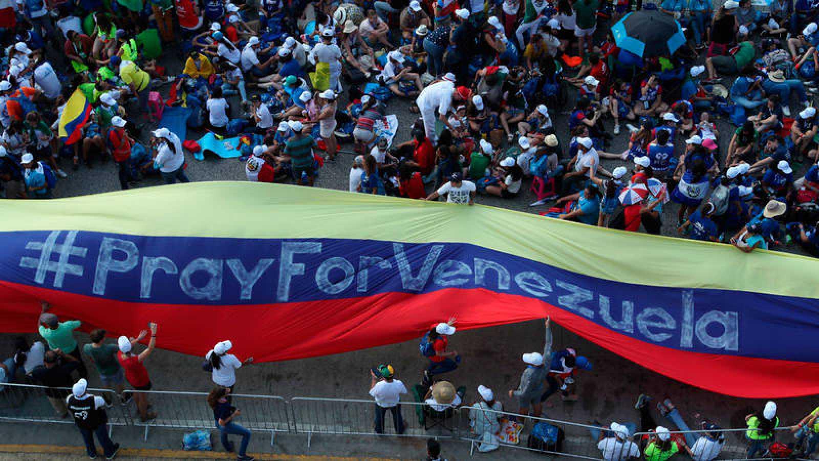 """Jóvenes peregrinos de la JMJ con una gran bandera venezolana en la que se lee """"Pray for Venezuela"""""""