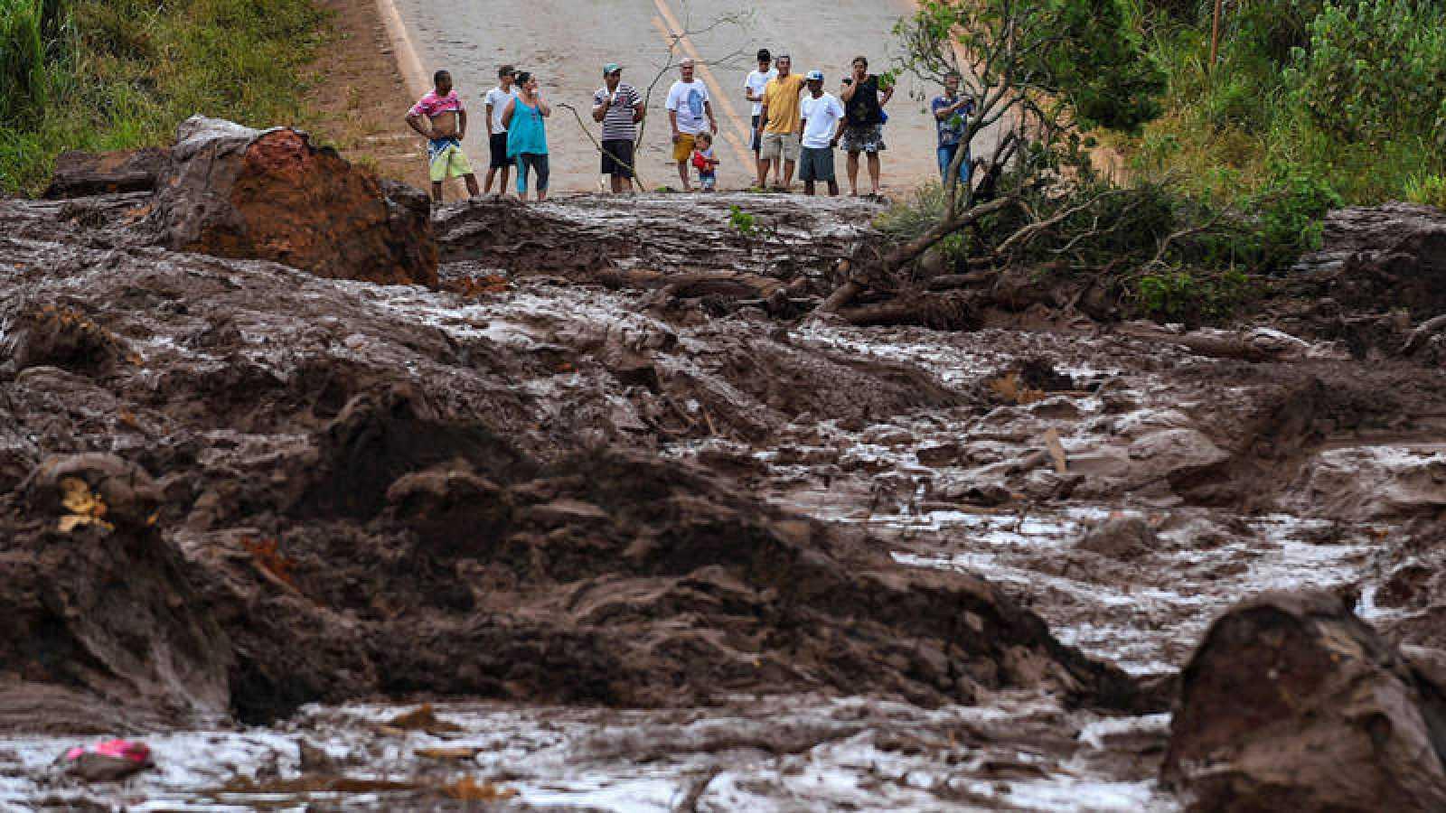 Un grupo de personas observa el desastre causado por la rotura de una presa que contenía residuos minerales de la compañía Vale