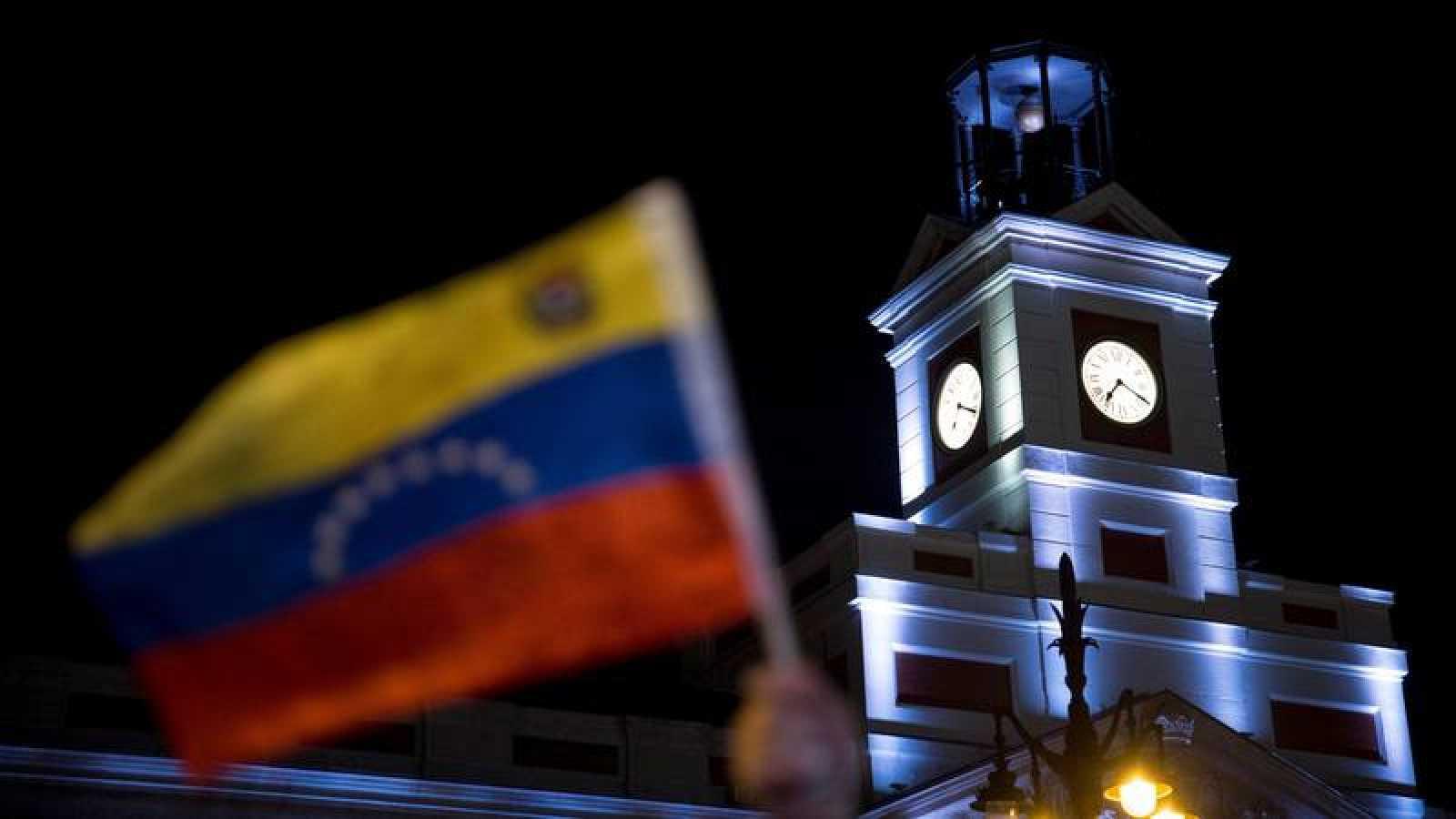 Manifestantes opositores ondean la bandera de Venezuela en la Puerta del Sol