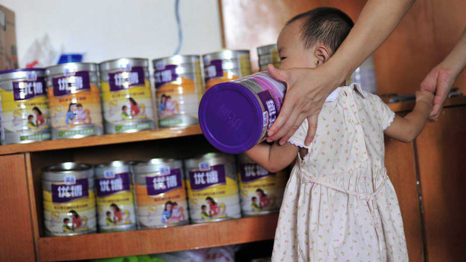 Imagen de una niña sosteniendo una lata de leche infantil en polvo.