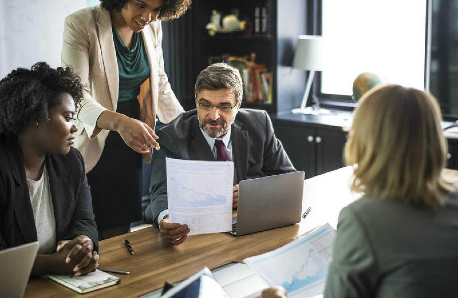 Fotografía de recurso de tres mujeres y un hombre trabajo en una oficina