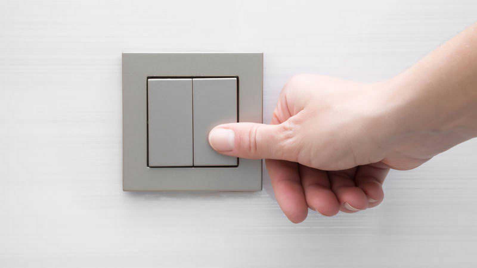 Imagen de archivo de una persona encendiendo un interruptor.