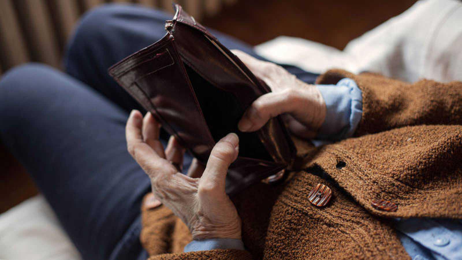 Una persona muestra la cartera vacía sentado en el sofá de su casa
