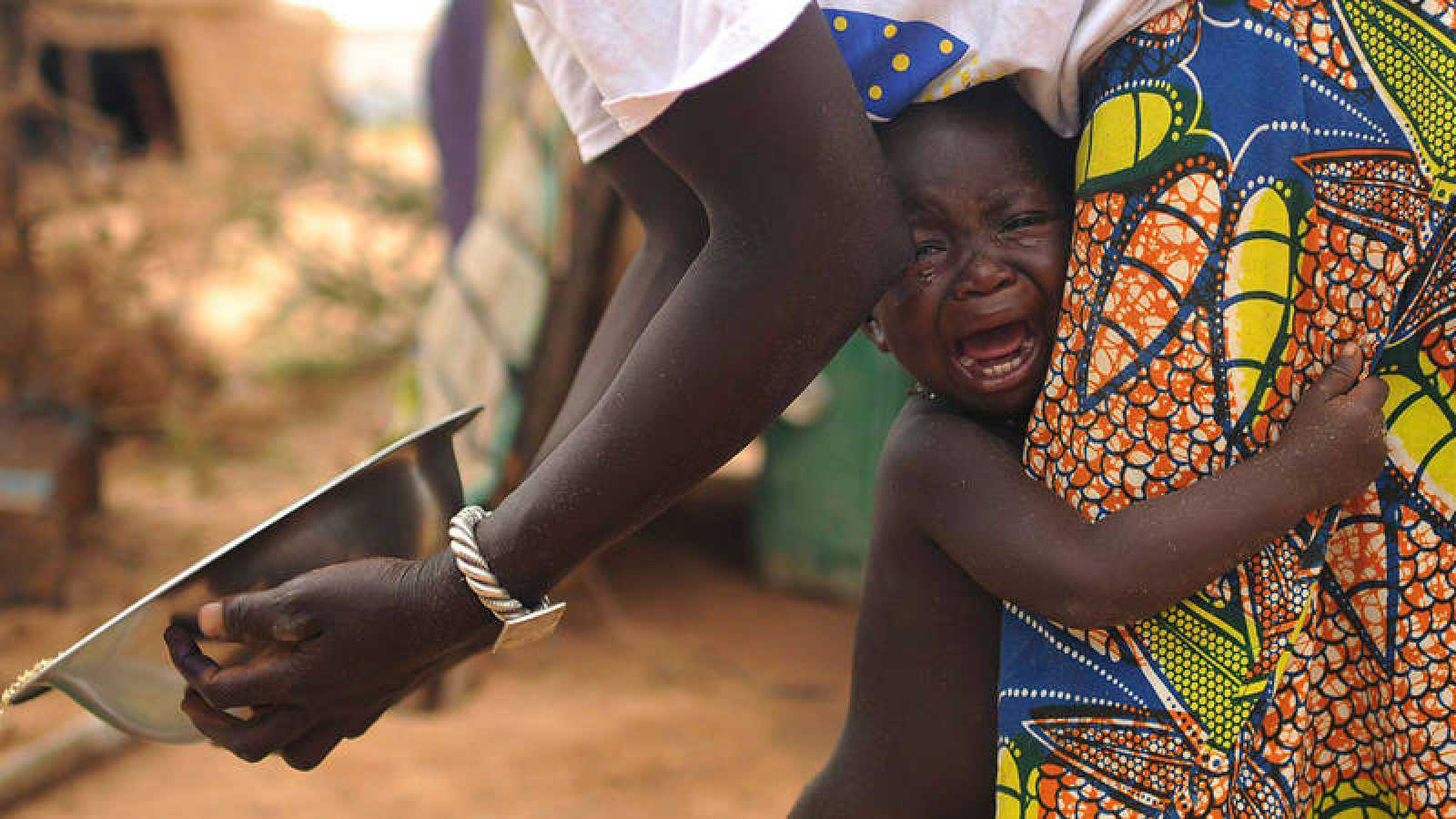 Una mujer con atuendo africano consuela en su regazo a un niño llorando.
