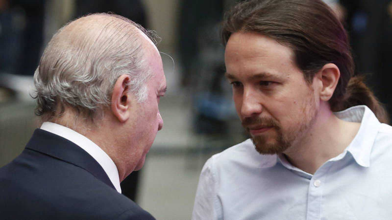 El líder de Podemos, Pablo Iglesias, conversa con el exministro de Interior Jorge Fernández Díaz