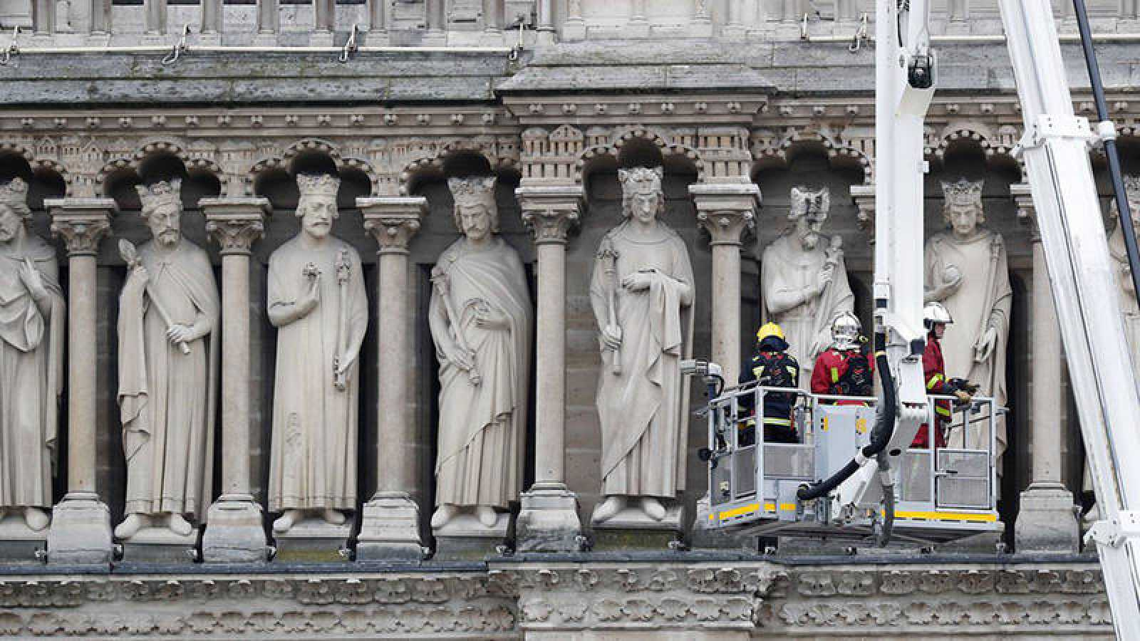 Varios bomberos trabajan en un elevador junto a varias esculturas de la fachada de Notre Dame
