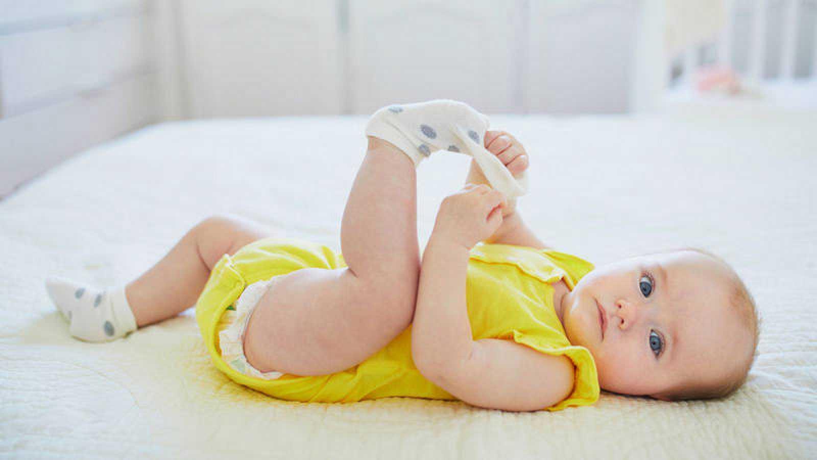 Un bebé juega con un calcetín