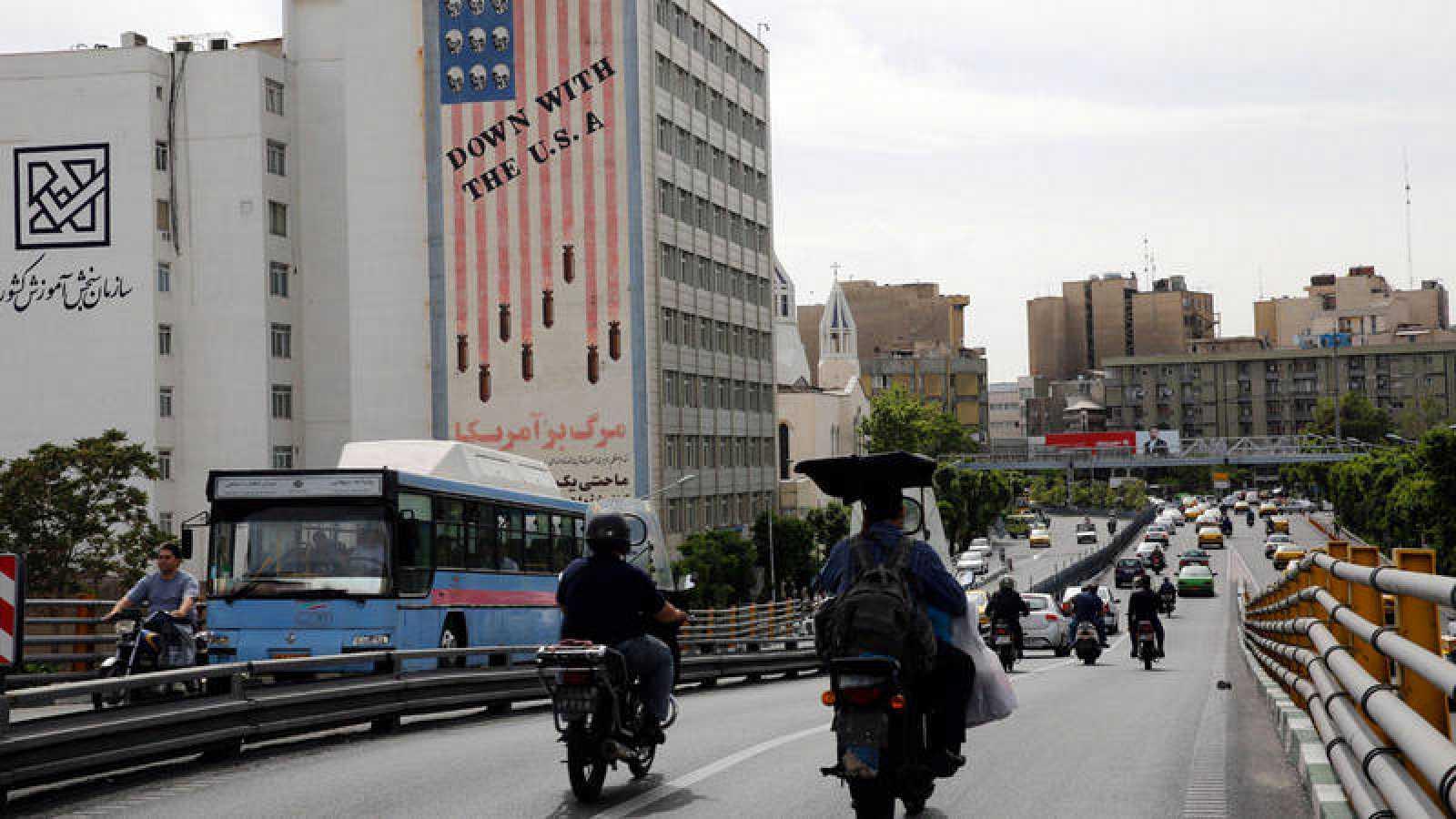 Conductores iraníes circulan junto a un edificio en el que aparece una pintada contra los Estados Unidos.