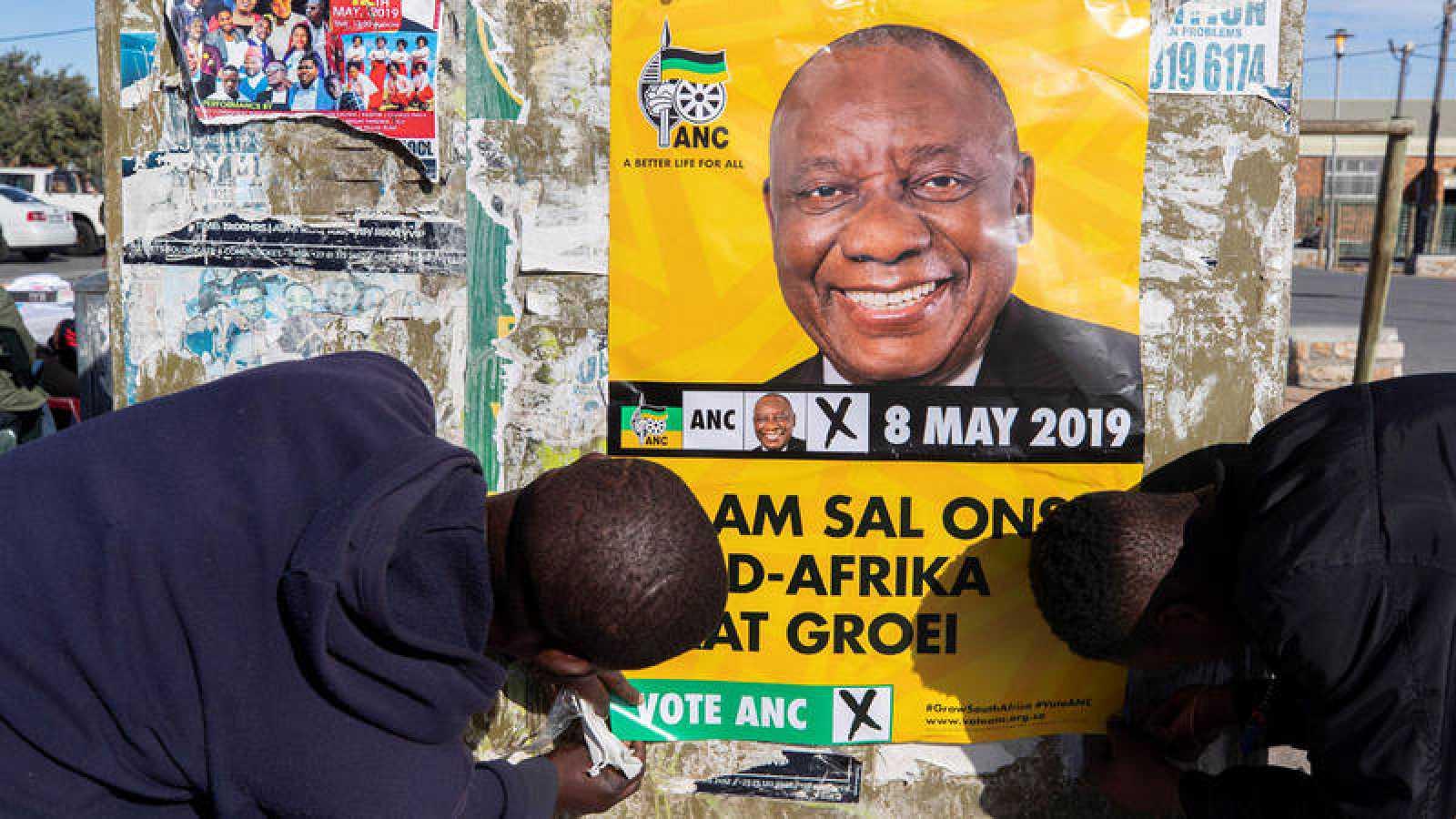 Un grupo de voluntarios colocan un cartel de Cyril Ramaphosa en Ciudad del Cabo