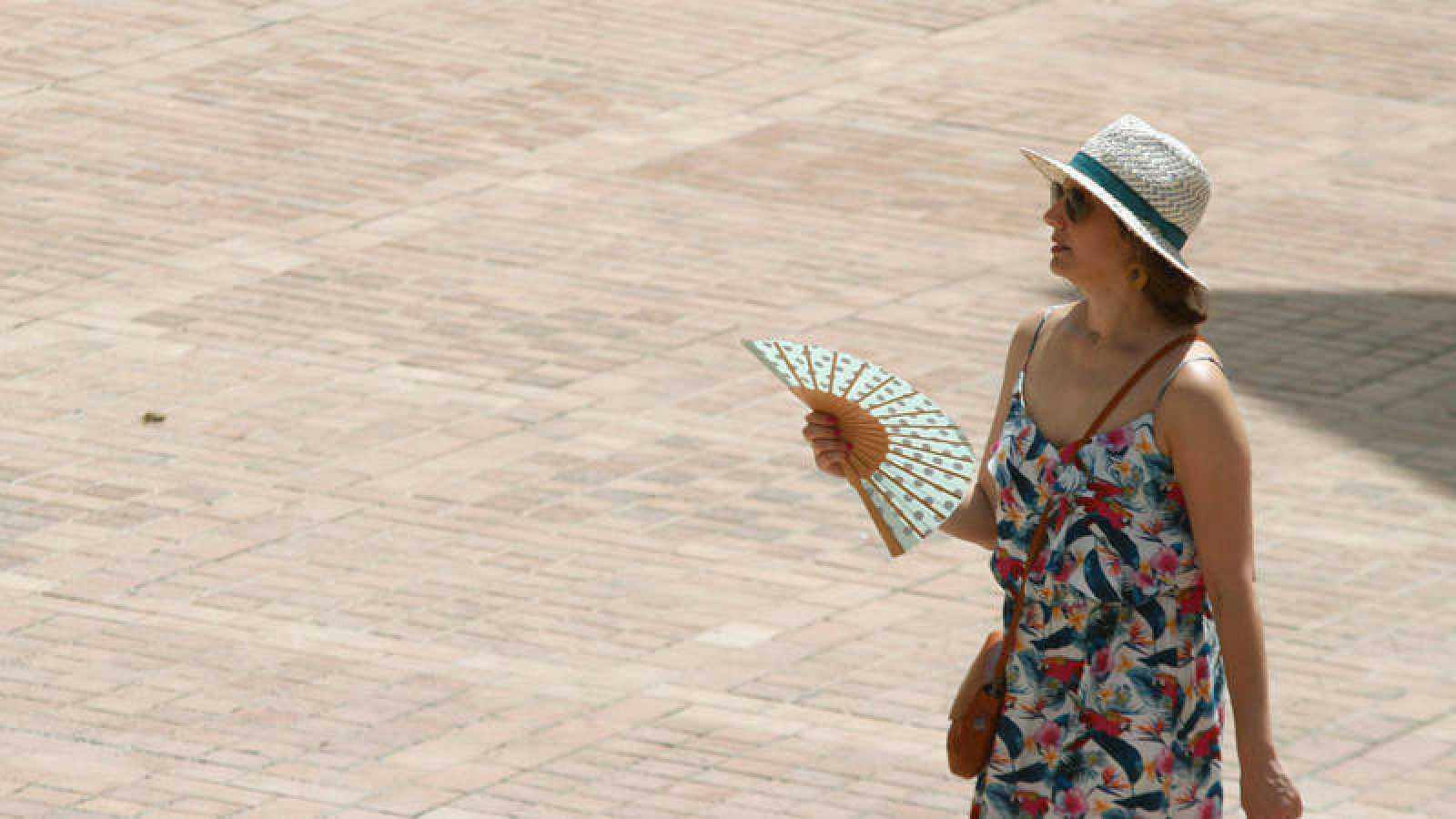Una mujer se abanica mientras camina por la calle en una jornada en la que las previsiones apuntan al aumento de las temperaturas.
