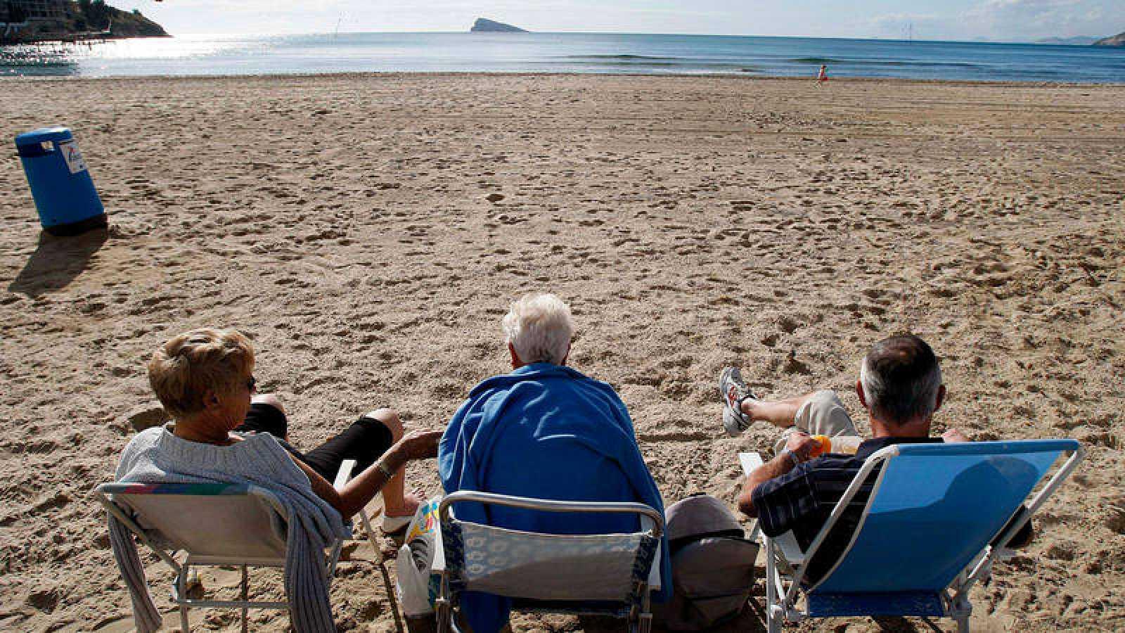 Tres personas disfrutan de un soleado dia en la playa de Levante de la localidad alicantina de Benidorm en una imagen de archivo