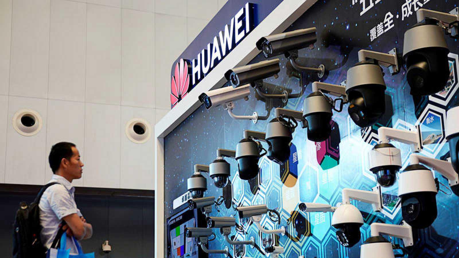 Un hombre observa varias cámaras de seguridad de Huawei