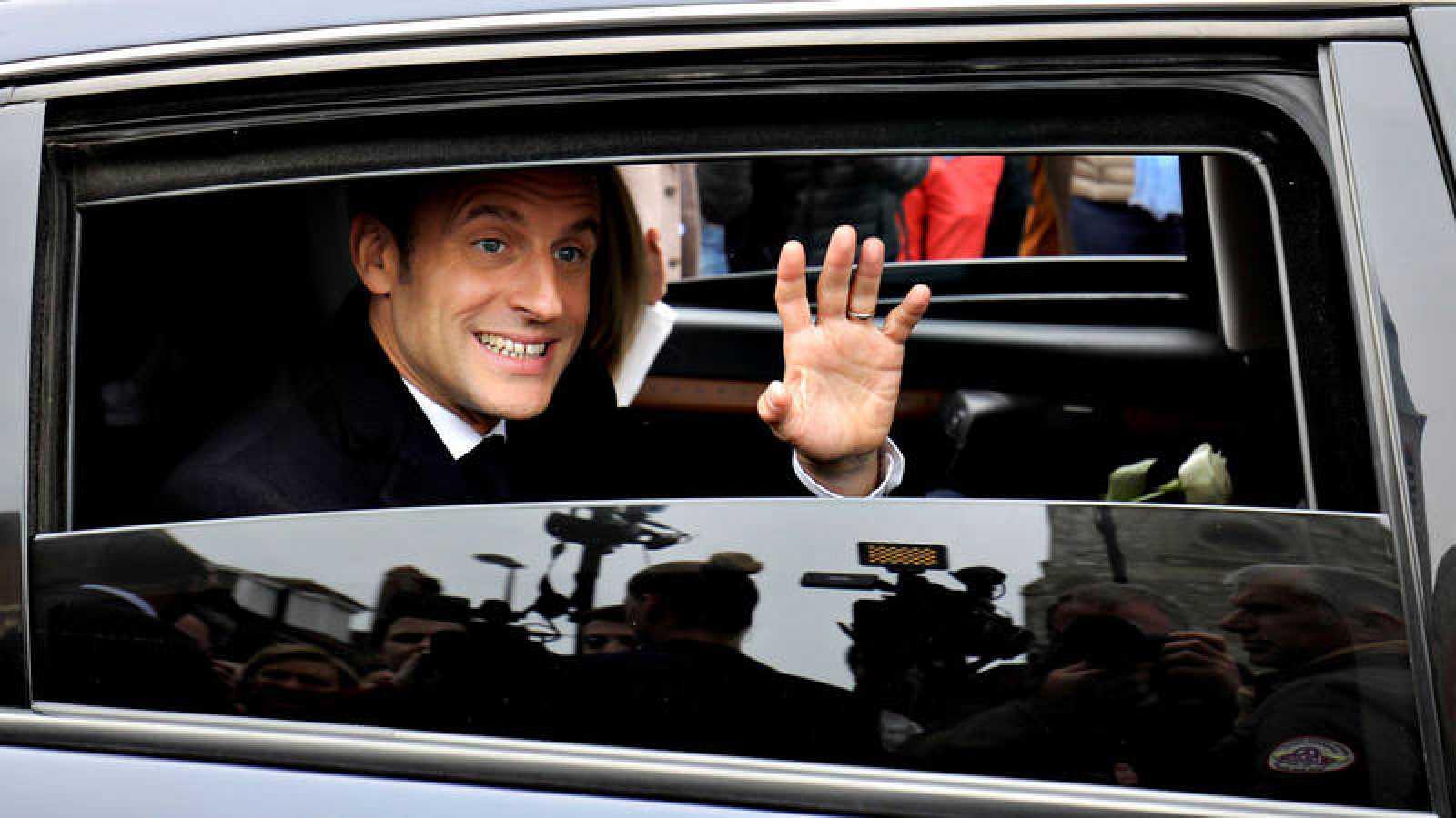 El presidente francés, Emmanuel Macron, saluda desde el coche oficial tras votar en las elecciones europeas