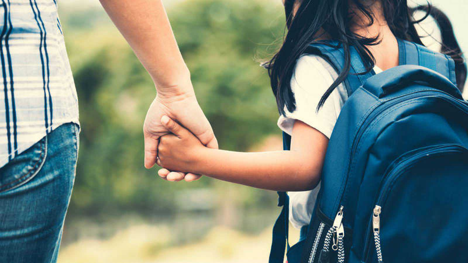 Una madre da la mano a su hija al salir del colegio