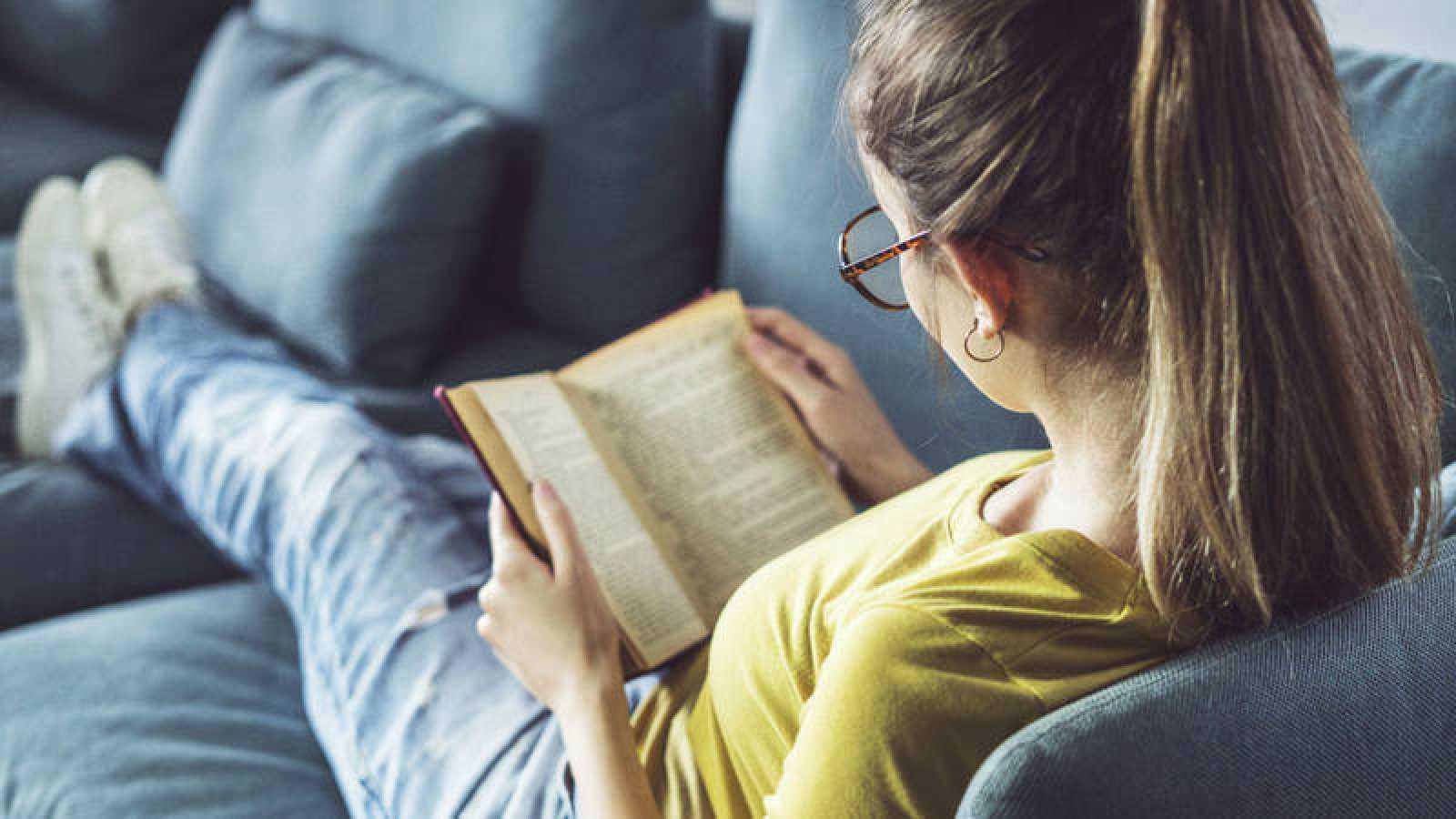 Una joven millennial lee una novela tumbada en el sofá.