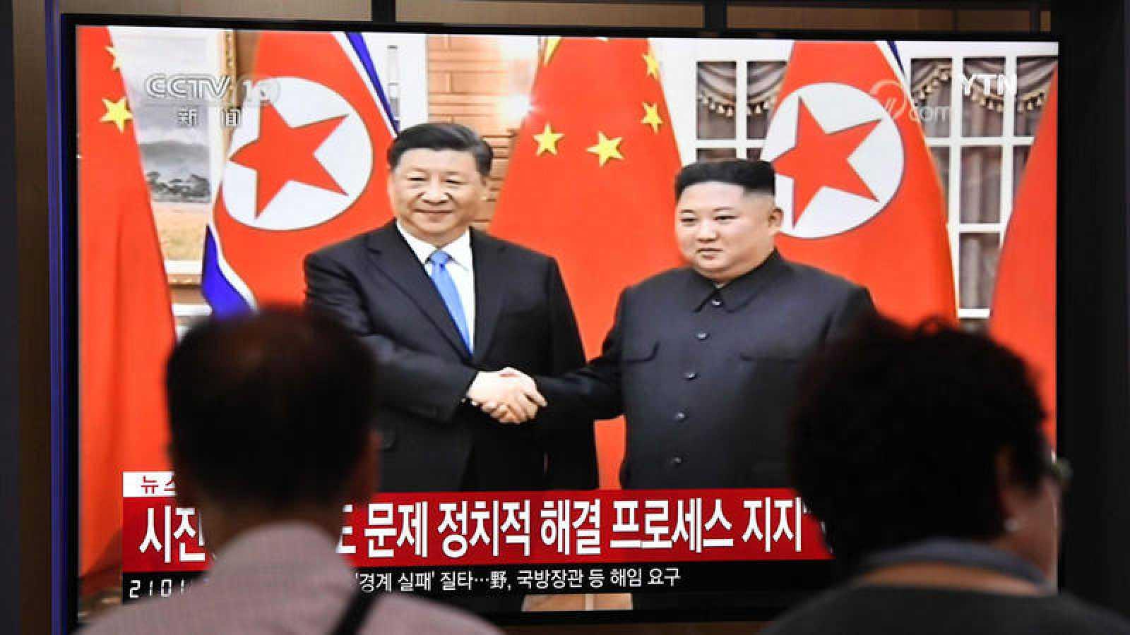 La gente ve una pantalla de noticias de televisión que muestra al líder norcoreano Kim Jong Un dándose la mano al presidente chino Xi Jinping, en la estación ferroviaria de Seúl