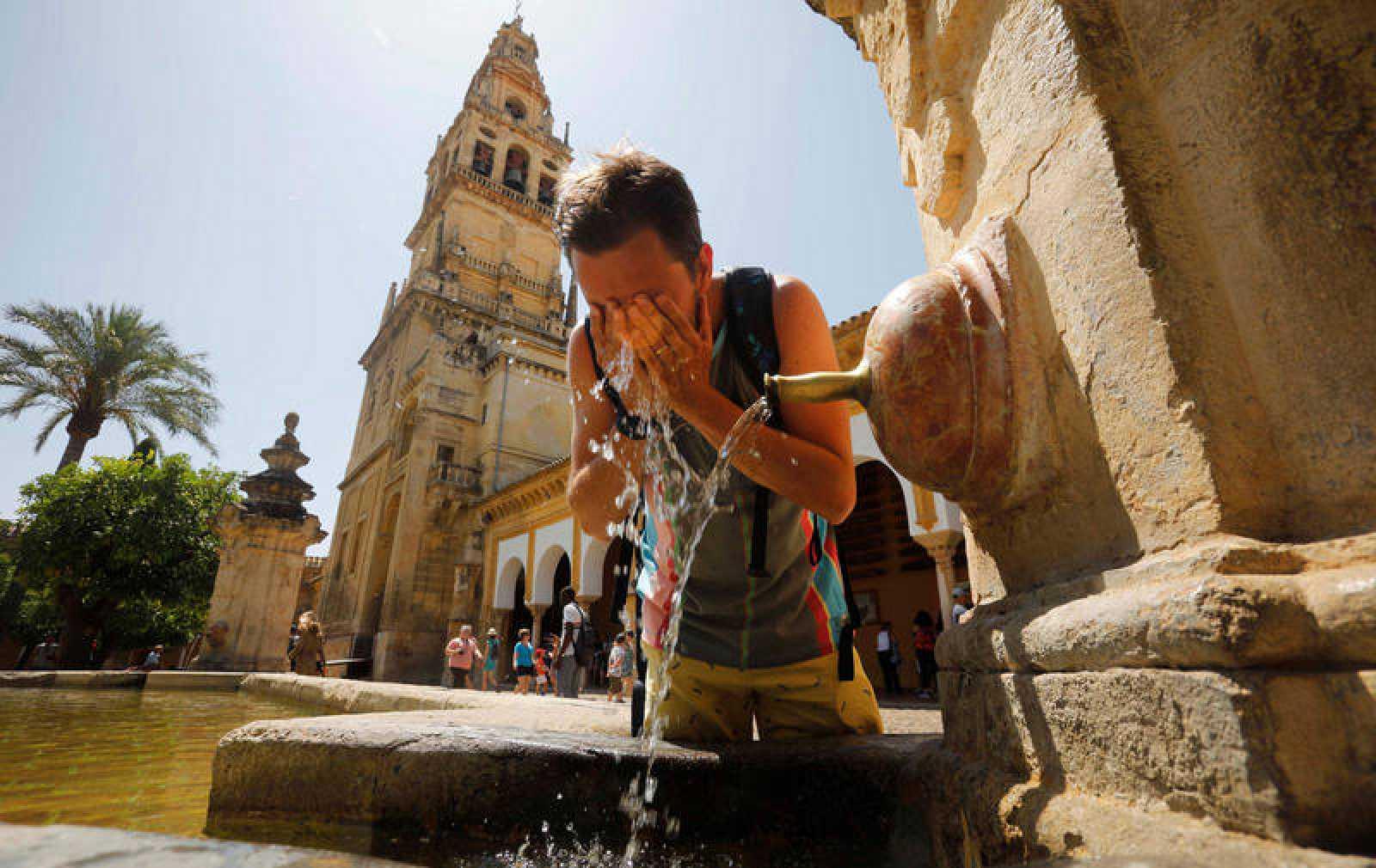 Un turista se refresca en una de las fuentes del patio de los Naranjos de la Mezquita-Catedral de Córdoba