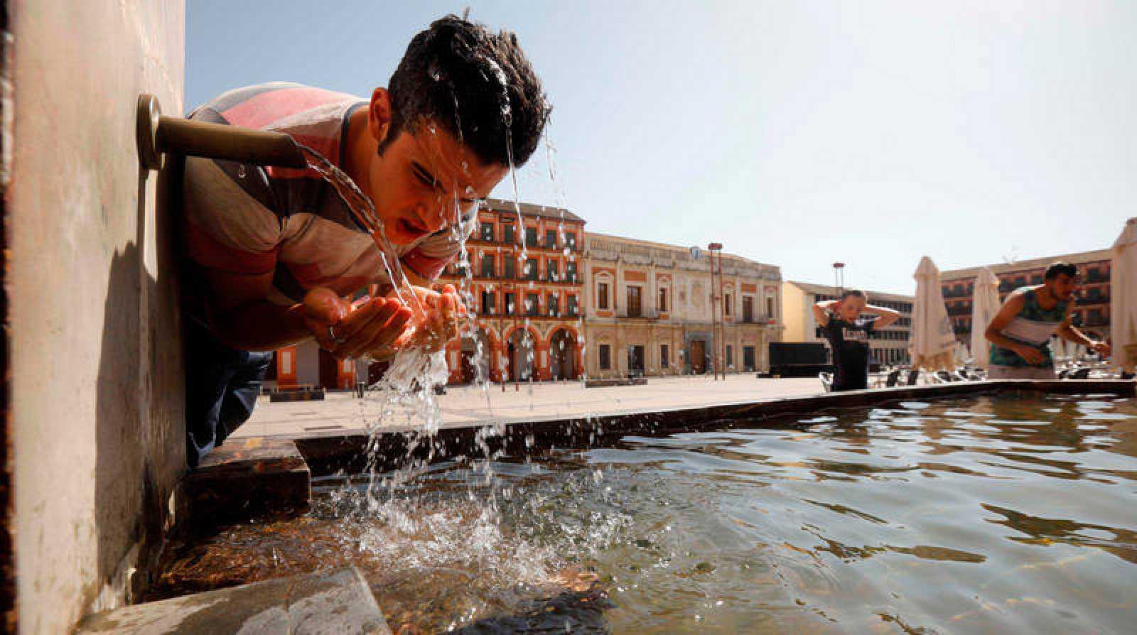 Un joven se refresca en la fuente del patio de los naranjos de la mezquita catedral de Córdoba este sábado.