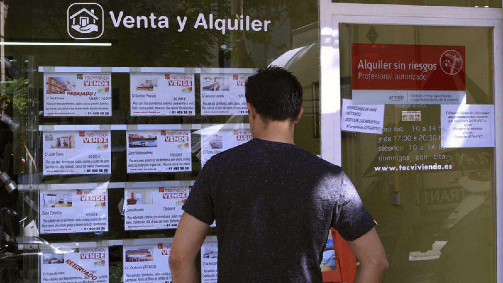 Un hombre mira el escaparate de una inmobiliaria en la que se anuncian pisos en alquiler y venta