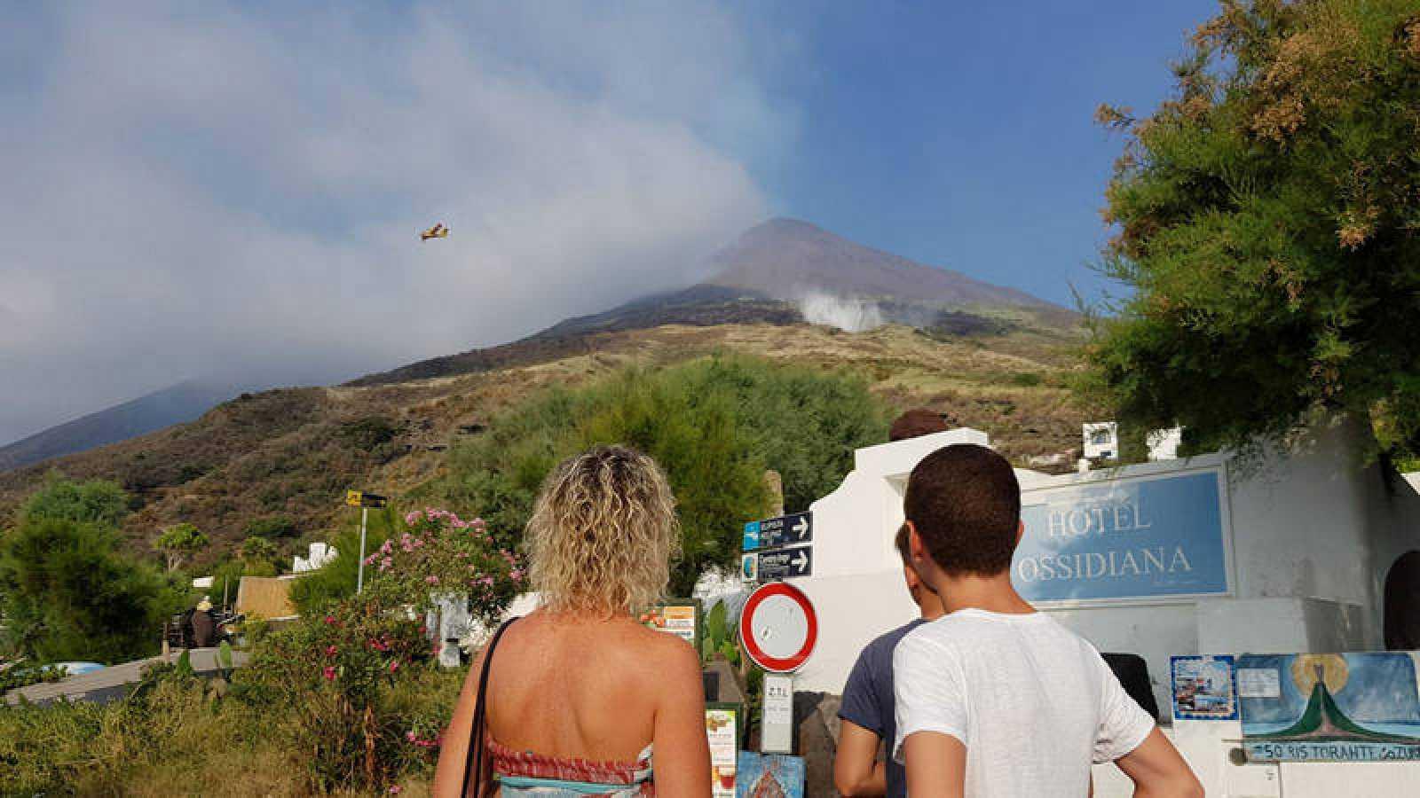 Dos turistas observan la actividad del volcán Estrómboli, un día después de la erupción