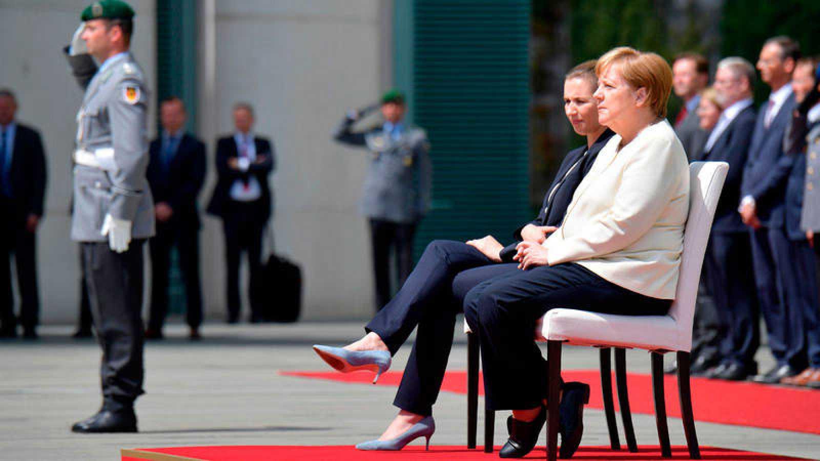 Angela Merkel escucha el himno sentada tras varios episodios de temblores