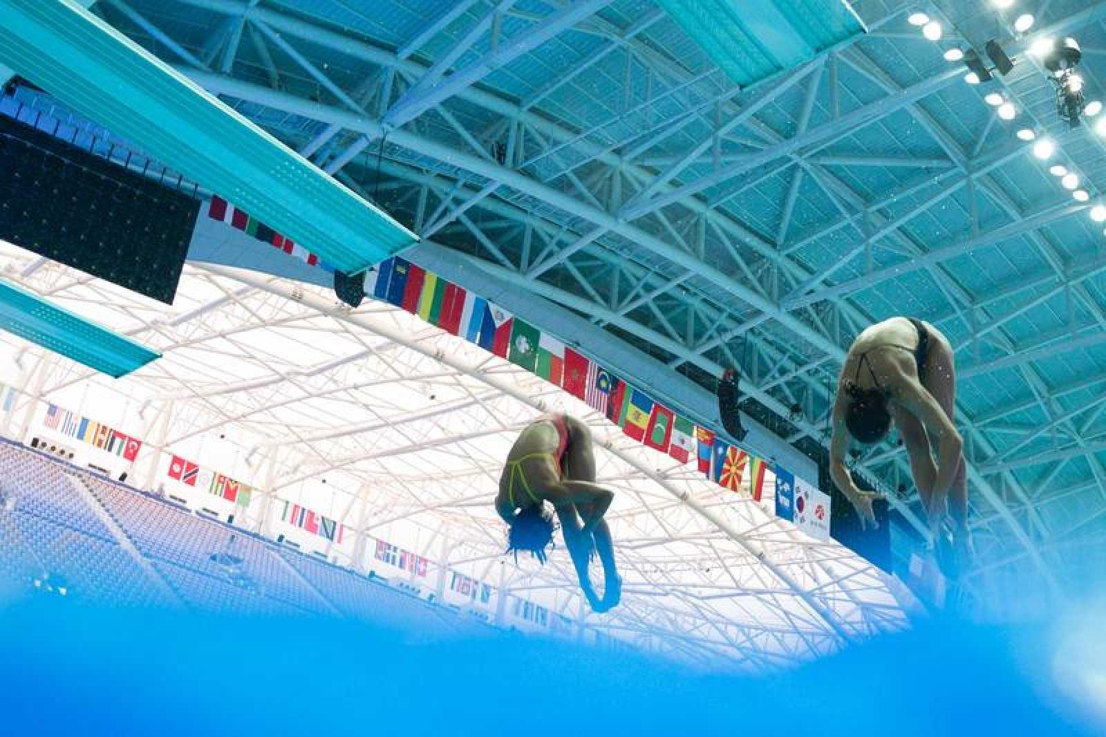 Dos saltadores entrenan saltos sincronizados en Gwangju
