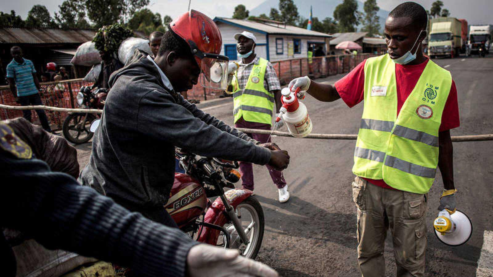 Un conductor se lava las manos en una estación de detección de ébola en la carretera entre Butembo y Goma