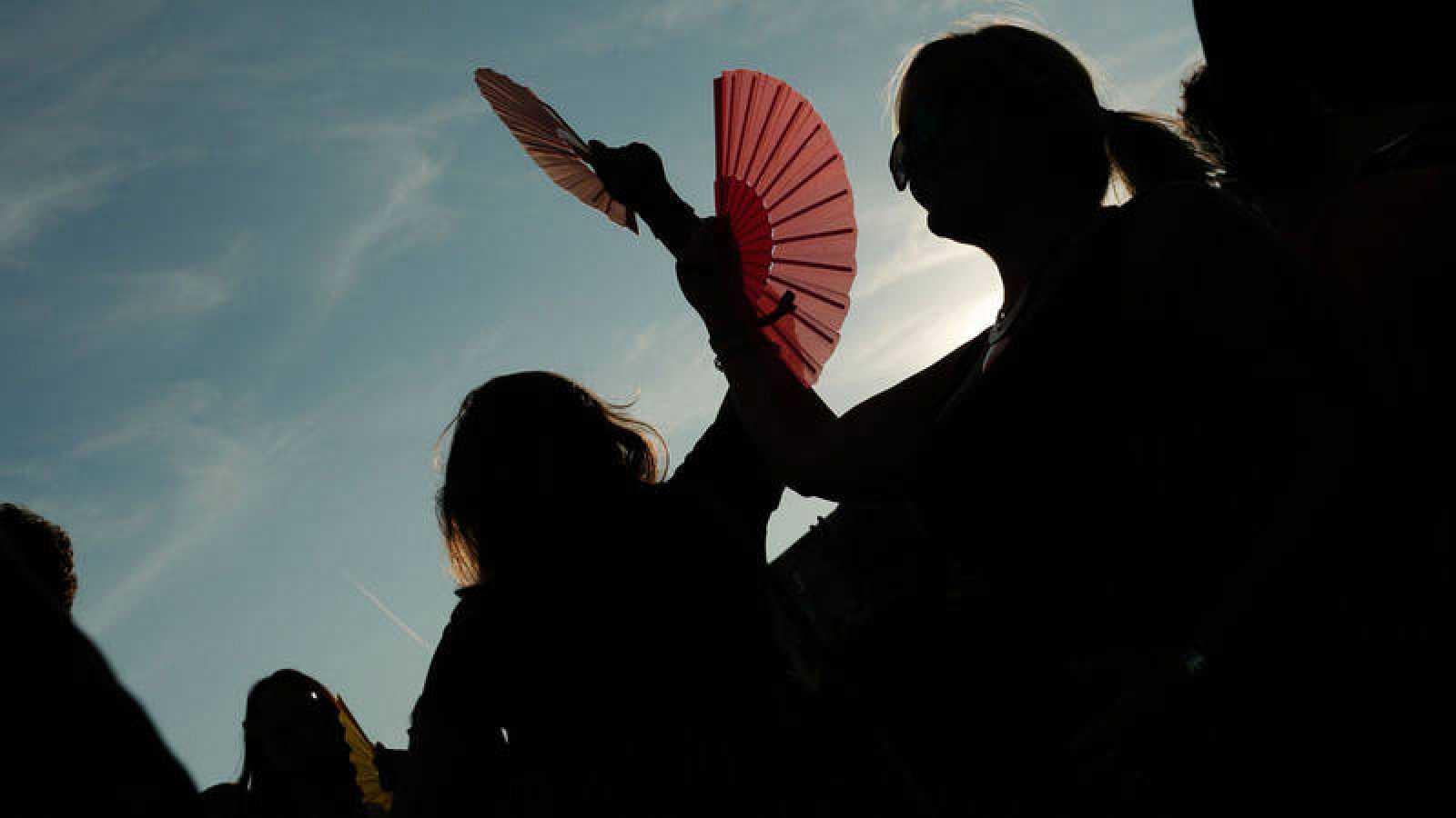 Varias mujeres combaten el calor con abanicos.