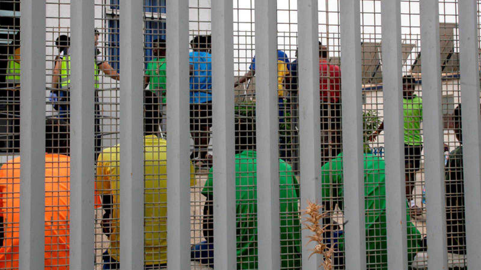 Un grupo de inmigrantes subsaharianos, tras el muro del Centro de Estancia Temporal de Inmigrantes (CETI)