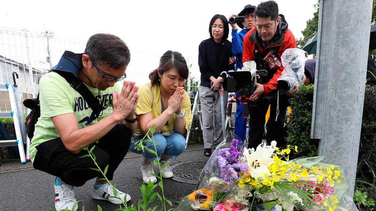 Un grupo de personas deposita flores en el exterior de los estudios Kyoto Animation, donde un incendio causó la muerte de decenas de personas.
