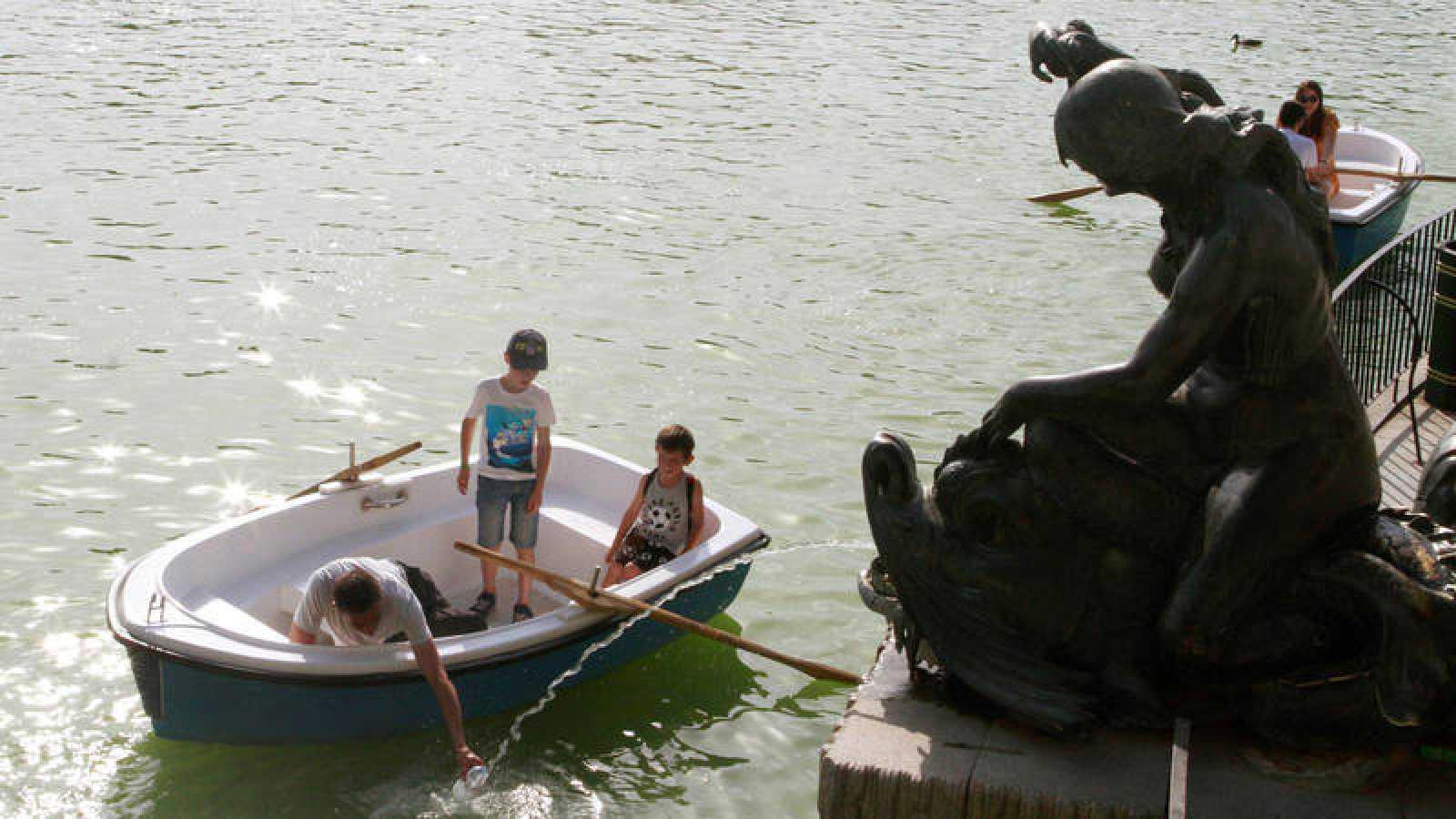 Un padre se refresca con sus hijos esta tarde en el parque de El Retiro de Madrid