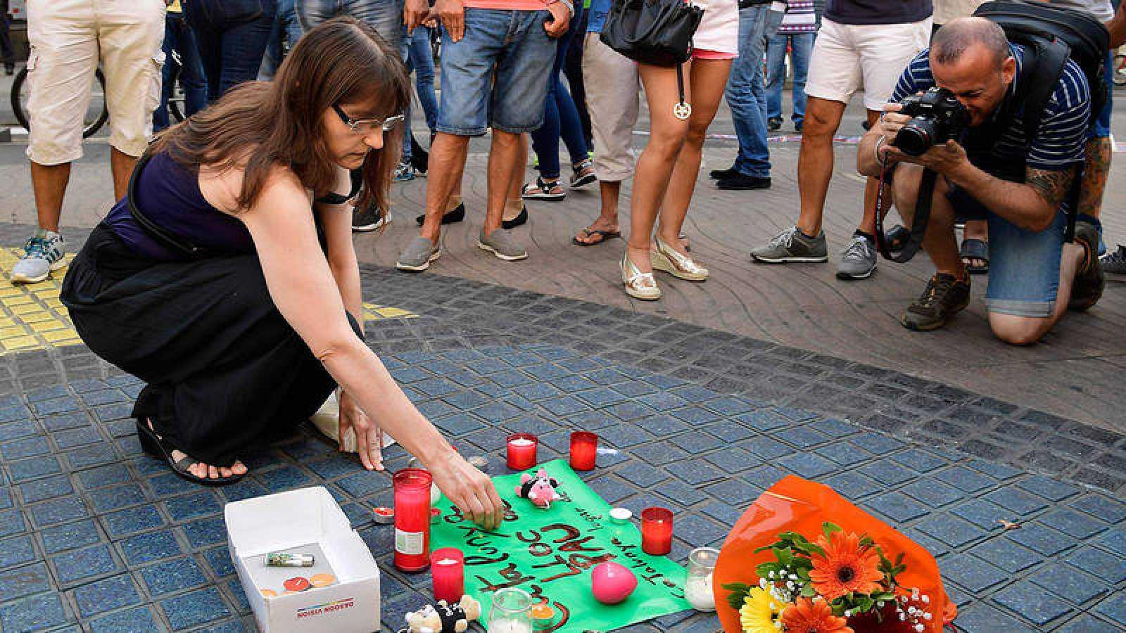 Una mujer deposita flores en memoria de las víctimas del atentado de Las Ramblas.