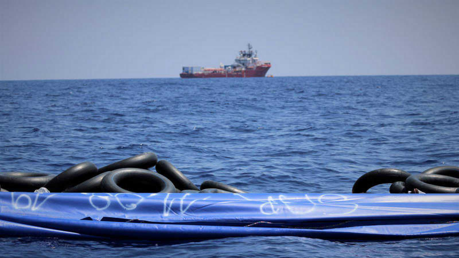 Una patera vacía flota en el Mediterráneo con el Ocean Viking en el horizonte