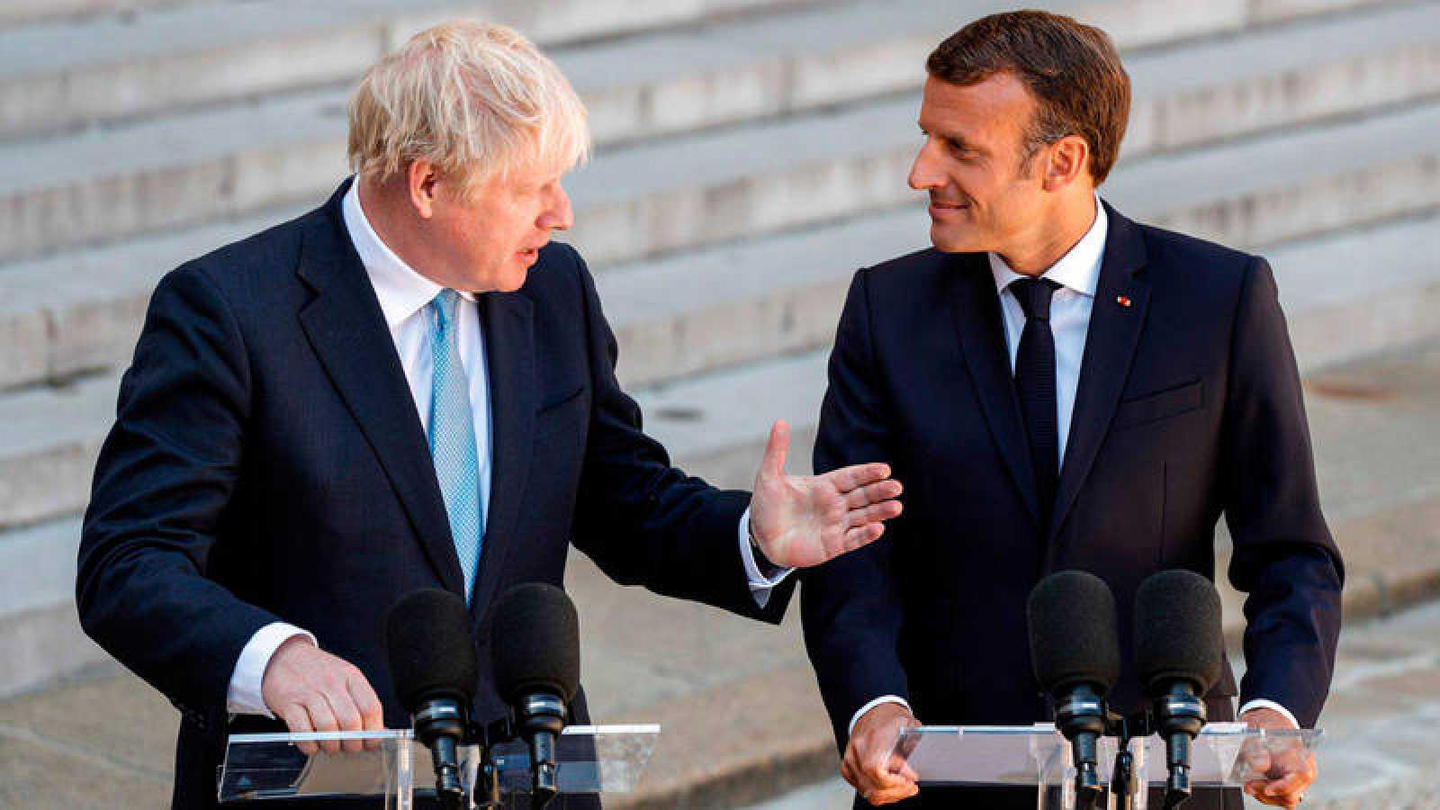 El presidente francés, Emmanuel Macron (R) y el primer ministro británico, Boris Johnson, hablan con los medios antes de su reunión en el Palacio del Elíseo en París