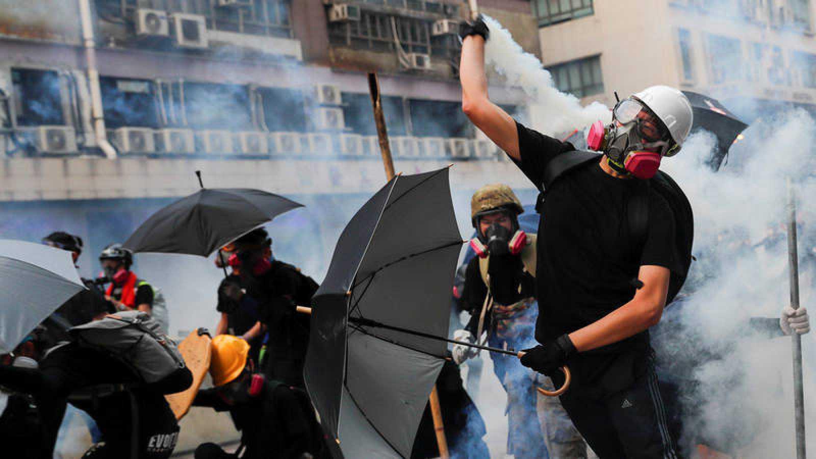Un manifestante arroja de vuelta un bote lacrimógeno a la policía