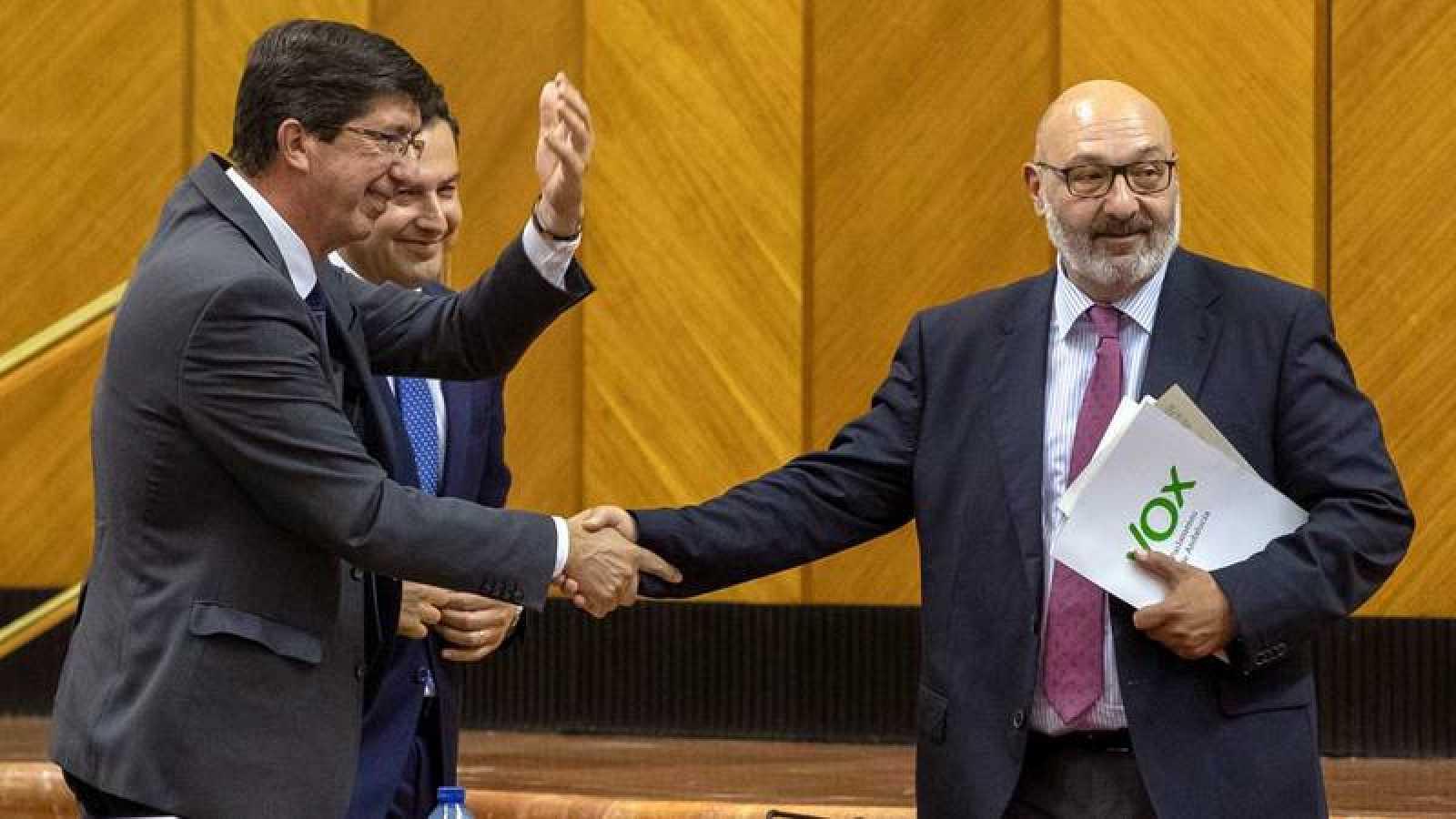 El vicepresidente de la Junta, Juan Marín (i), de Ciudadanos, hace un gesto a la bancada socialista mientras el presidente andaluz, Juanma Moreno y el portavoz de Vox, Alejandro Hernández (d), se dan la mano en el Parlamento de Andalucía