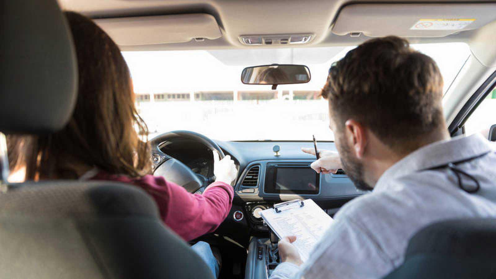 Un examinador realiza indicaciones a una aspirante a obtener el carné de conducir